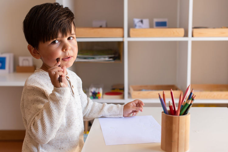 Portrait of boy holding paper at home