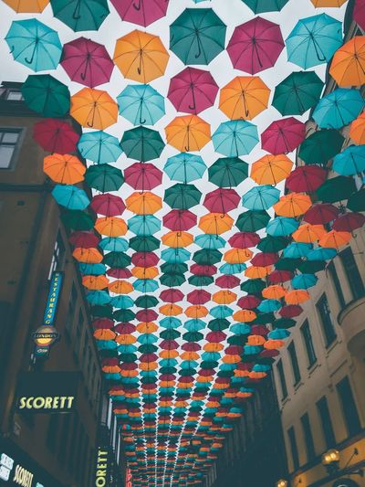 Low angle view of multi colored umbrellas hanging amidst buildings in city