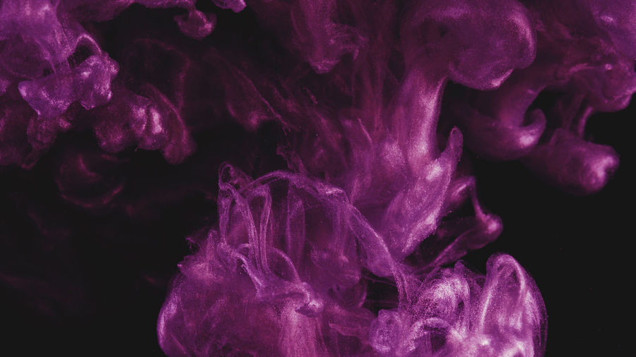 Close-up of purple liquid over black background