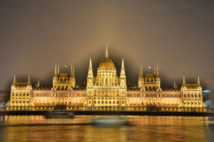 Illuminated Hungarian Parliament Building By River At Night