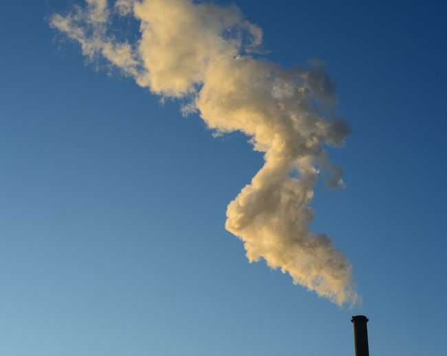Low angle view of chimney emitting smoke against sky
