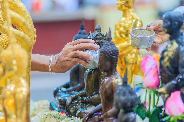 Cropped image of hand pouring water on buddha statue