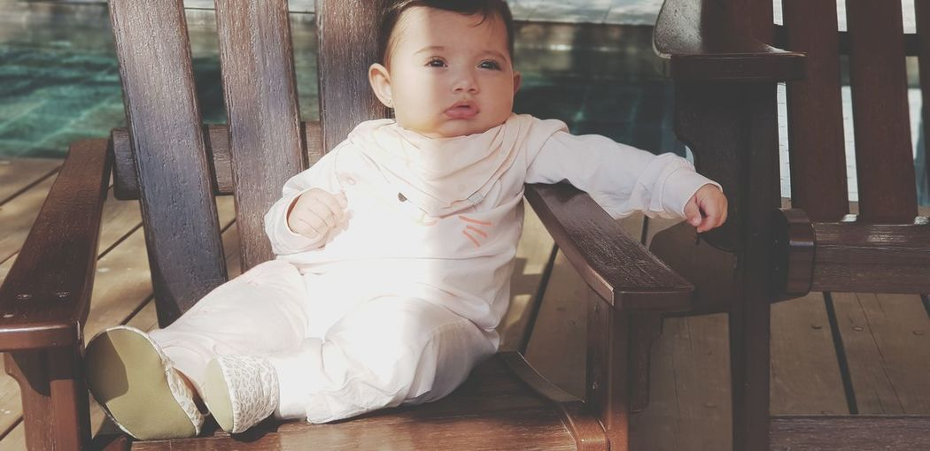 Cute Baby Girl Sitting On Chair