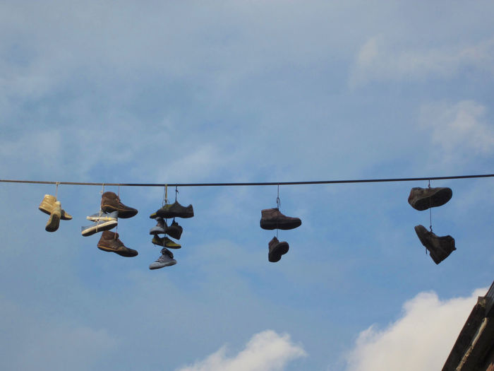 seven pair of shoes hanging on an electricity cable above the street against a blue sky Shoes Sky Street Pair Sneakers Fun Blue Cable Electricity  Sport Laces Cloud - Sky Hanging Outdoors No People Large Group Of Objects Shoe Side By Side Day