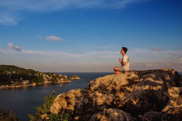 Meditation Paradise Relaxing Belvedere Viewpoint Meditation Yoga One Person Water Sky Solid Rock Real People Nature Day Outdoors Side View