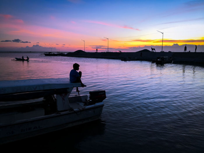 Silhouette man on boat against sky during sunset