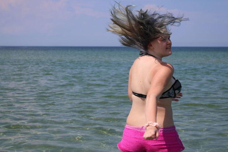 Beautiful woman standing in sea against sky