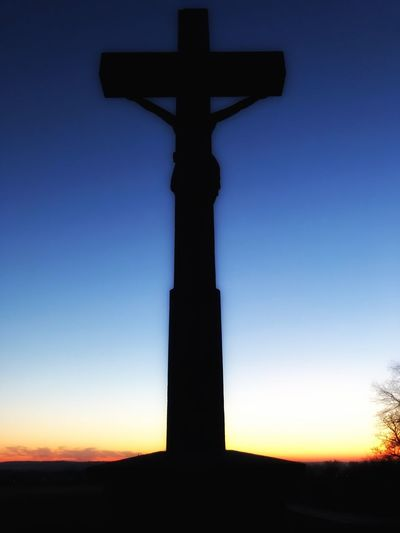 Low angle view of silhouette cross against blue sky
