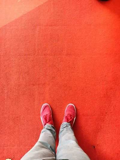 Low Section Of Man Standing On Red Floor
