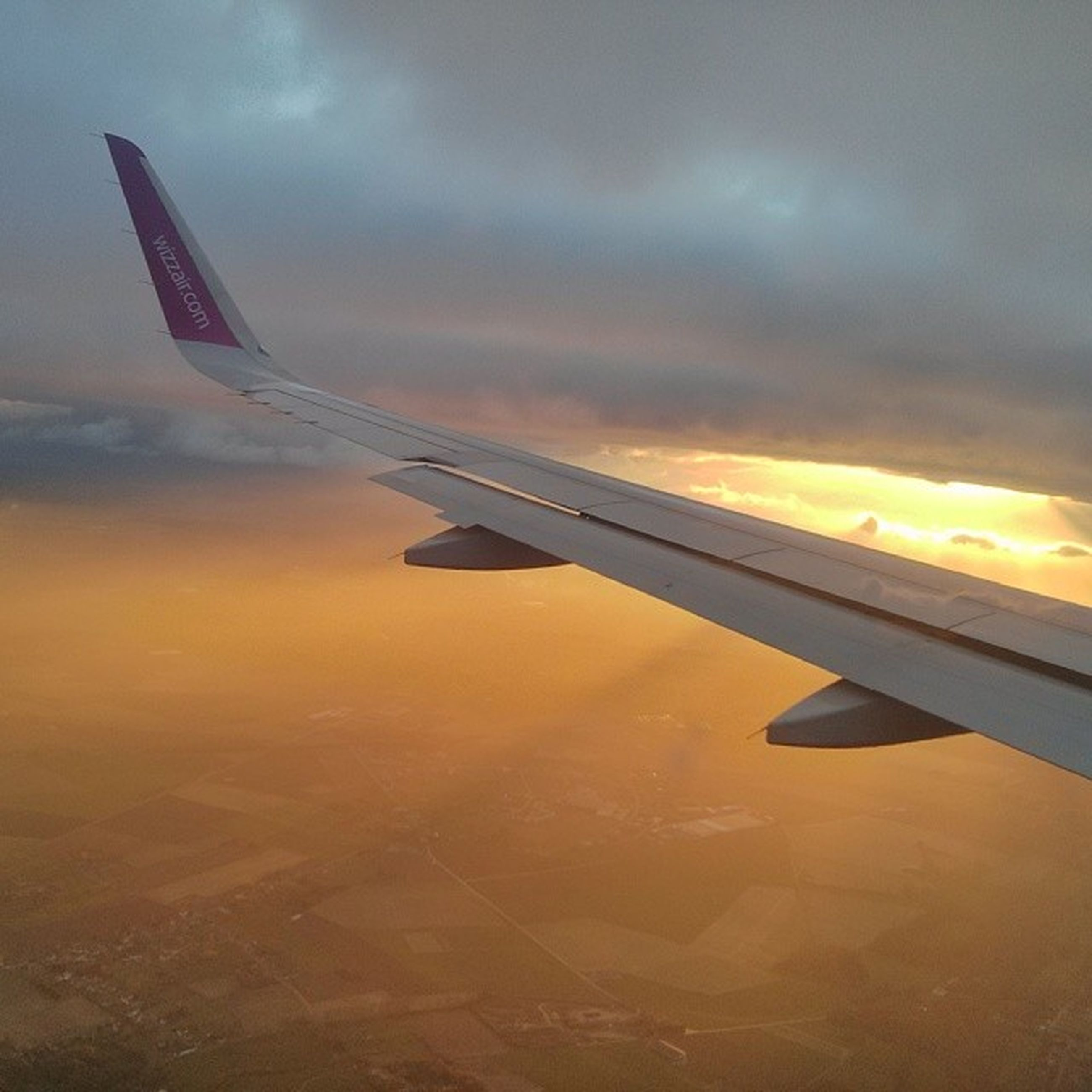 airplane, aircraft wing, air vehicle, transportation, flying, mode of transport, sunset, sky, cropped, part of, aerial view, cloud - sky, mid-air, travel, on the move, public transportation, orange color, airplane wing, journey, no people