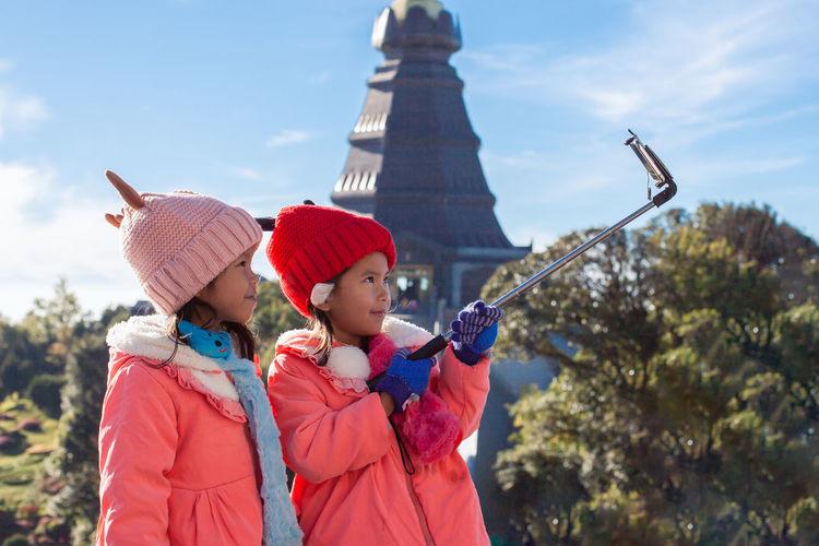 Cute Siblings Wearing Warm Clothing Taking Selfie In City
