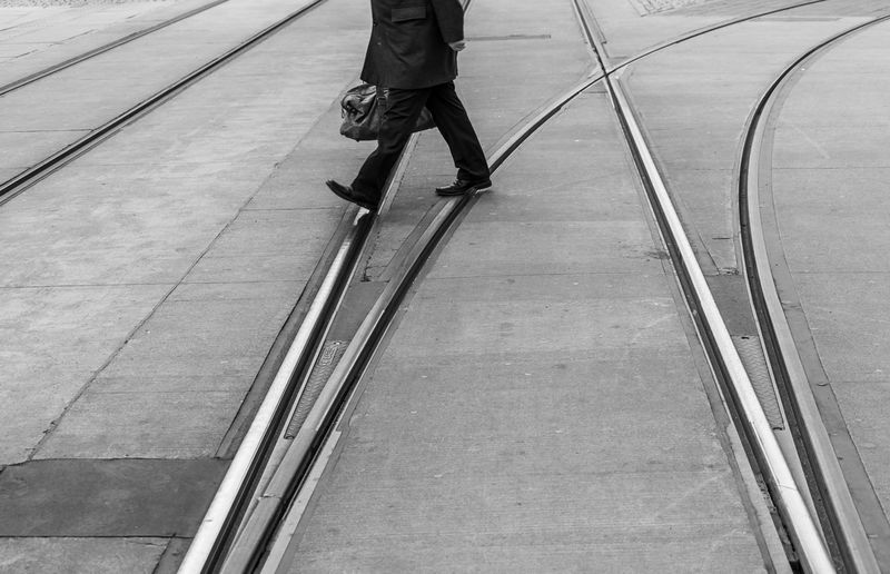 Black And White Street Photography City Rails Tramway Railway Real People One Person Lifestyles Low Section Walking Human Leg Men Day Body Part Human Body Part Leisure Activity Motion High Angle View Unrecognizable Person Outdoors on the move Footpath Architecture Streetwise Photography