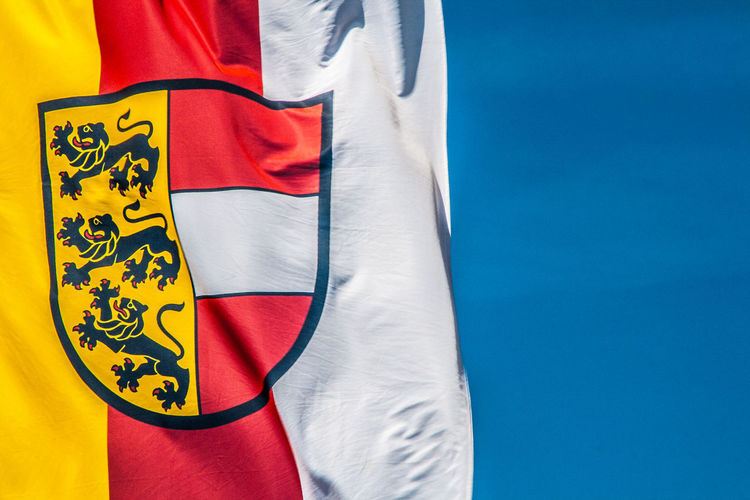 Low angle view of carinthia flag with coat of arms against blue sky