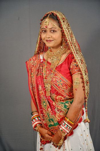 Portrait of smiling young bride standing against wall