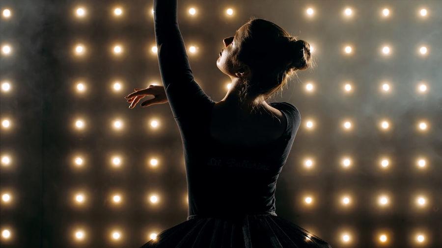 Ballerina dancing against illuminated lights