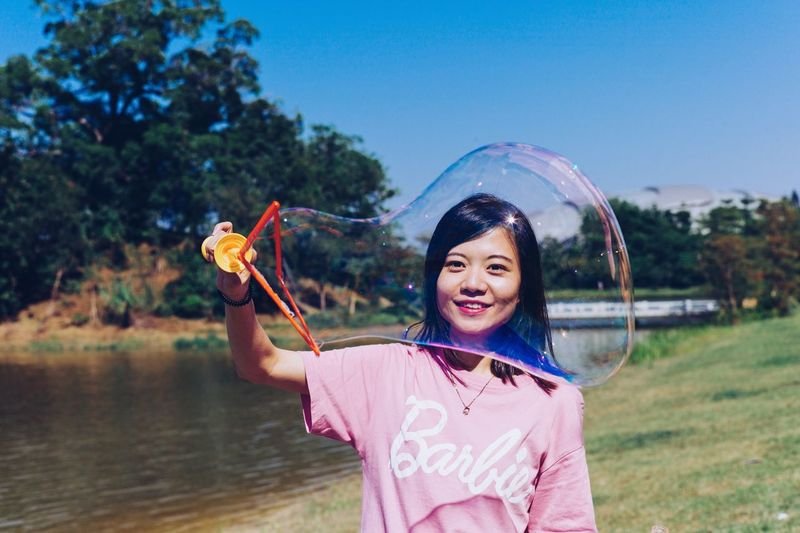 Portrait Of Smiling Young Woman Making Bubble At Lakeshore