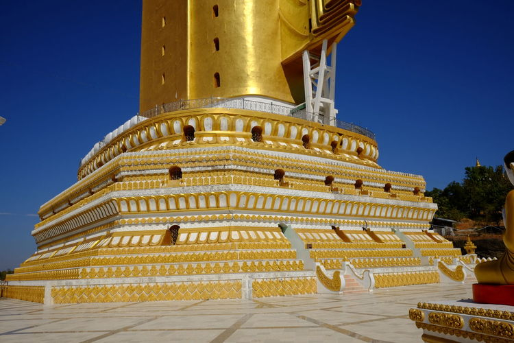 Base of Bodi Tataung Giant Standing Buddha (424ft) - known as Lakyun Setkar said to be the second largest buddha in the world Blue Sky Bodi Tataung Giant Buddhas Buddhism Buddhist Architecture Buddhist Art Buddhist Culture Building Exterior Clear Sky Composition Full Frame Gold Coloured History Low Angle View Monywa Myanmar No People Outdoor Photography Plinth Religion Second Largest Buddha In The World Sunlight Tourism Travel Destination Travel Destinations Tree