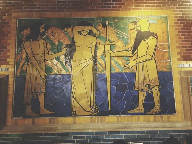 A woman is being sold and other slaves are in the background of this Jan Toorop 1903 mosaic in the Berlage Beurs that he called 'Past'.