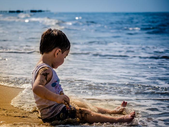 Full Length Of Cute Boy Sitting At Beach