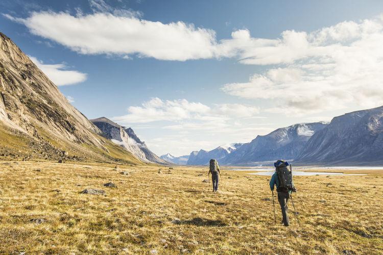 Rear view of men walking on field against sky