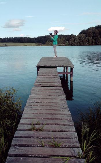 Teenage Girl Standing On Pier At Lake