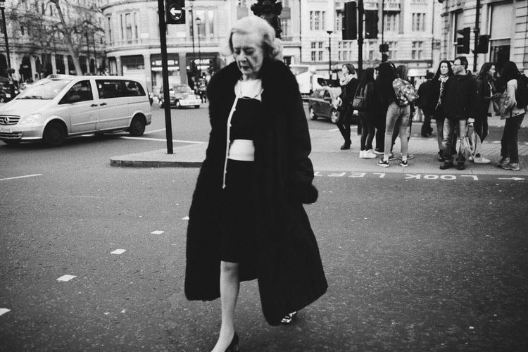 Woman standing on road in city