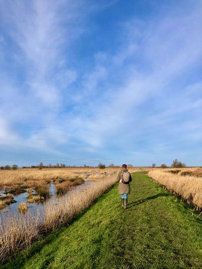 Rear view of woman walking on field against sky