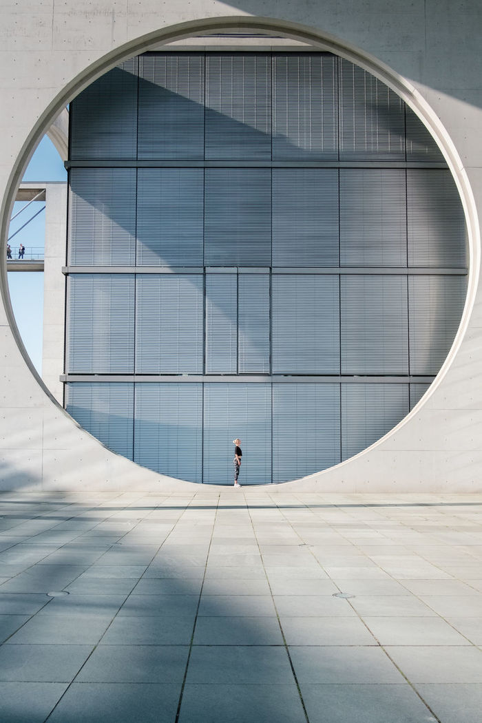 Woman standing on circle against building