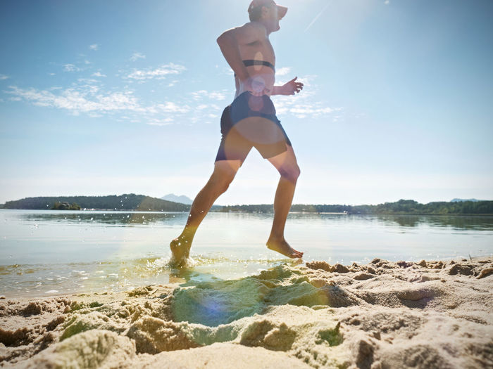 Man checking pulse trace on heartbeat monitor while running in water of lake. funy sport activities