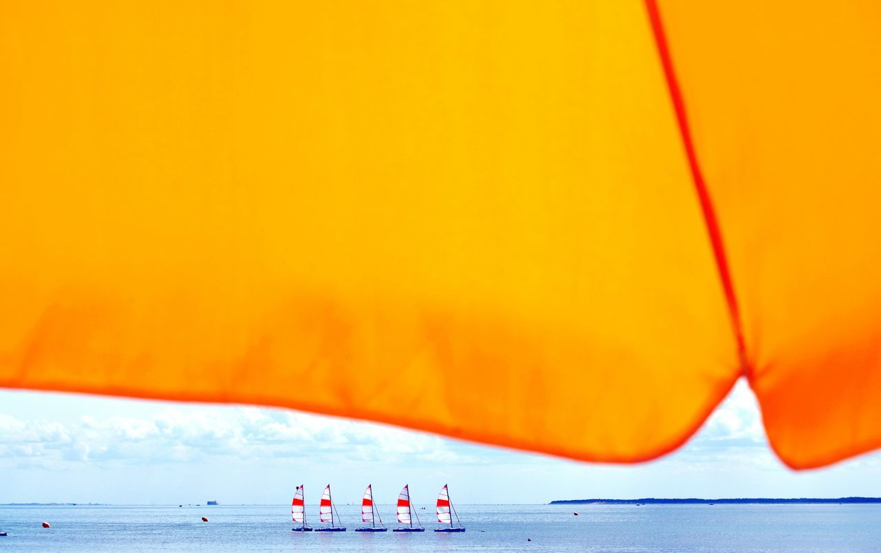 Close-up of parasol against boats on sea