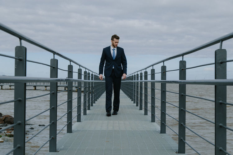 Businessman Walking On Pier Over Sea Against Sky