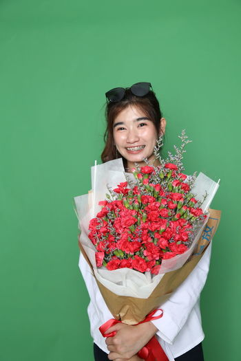 Portrait of a smiling woman holding red flower