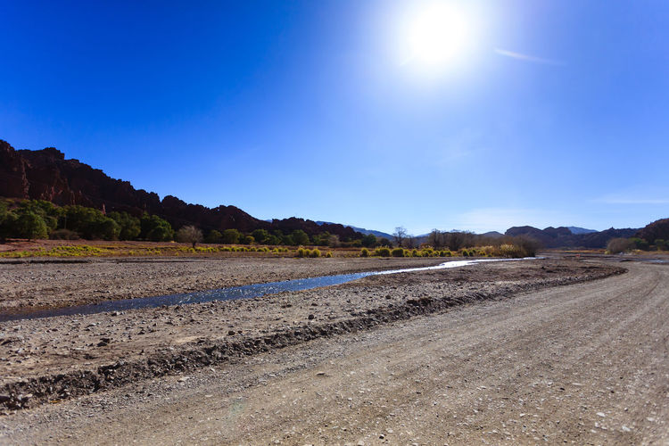 Scenic view of road by field against clear blue sky