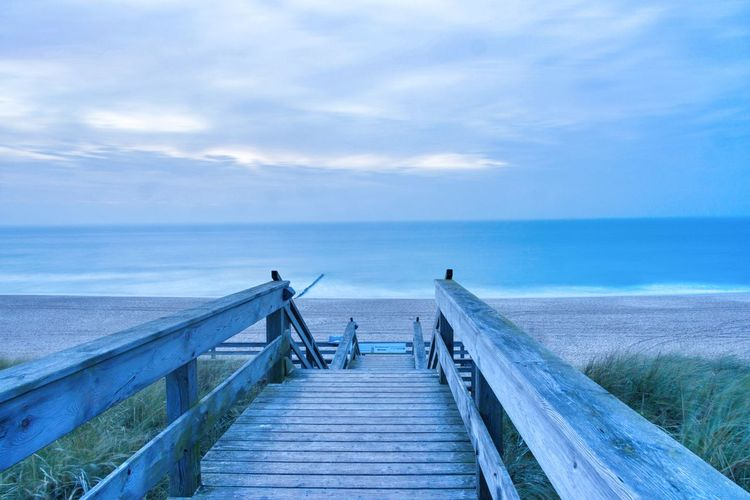 View of wooden pier on sea against sky