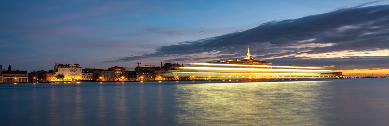Blurred Motion Of Illuminated Cruise Ship On Sea By City At Dusk
