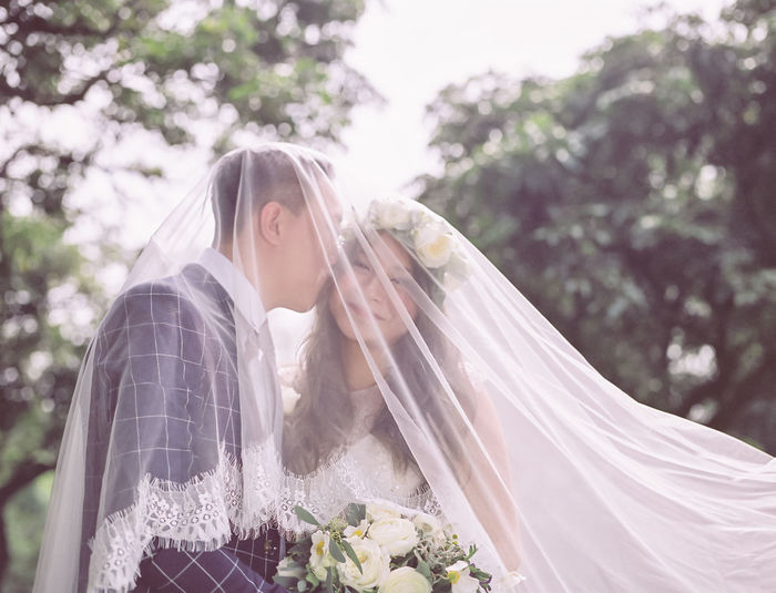 Groom Kissing Smiling Bride Under Veil