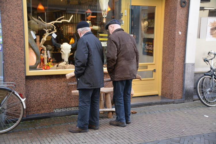 Rear view of men standing on street and looking at retail display