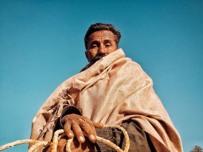 Low angle portrait of man wearing shawl against clear blue sky
