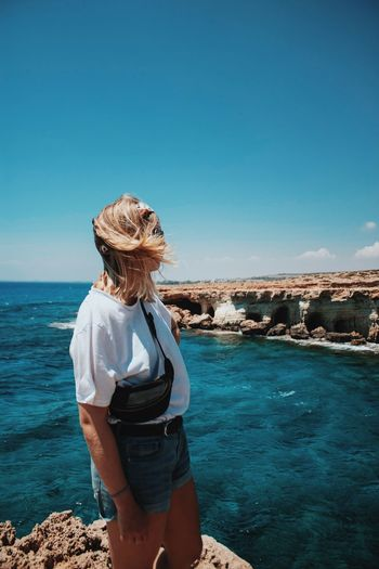 Water Sea Sky One Person Real People Lifestyles Leisure Activity Rear View Standing Nature Women Beauty In Nature Three Quarter Length Scenics - Nature Looking At View Horizon Over Water Outdoors Clear Sky Hair Hairstyle Trip Land Blue