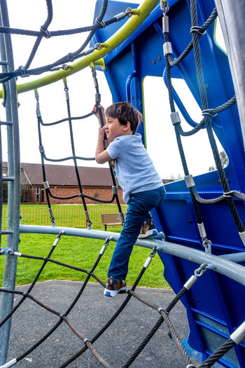 A young boy plays in a climbing frame in a children's playground. Adventurous Brave Fun Happiness Happy Young Boy Boys Bravery Child Childhood Climbing Climbing Frame Full Length Innocence Leisure Activity Net Netting One Person Outdoor Play Equipment Outdoors Playground Playing Real People Risk Taker