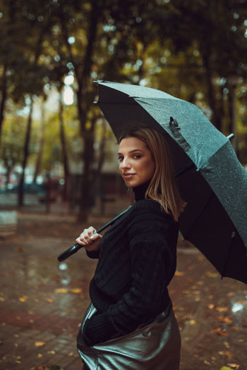 Portrait of smiling young woman holding umbrella in park