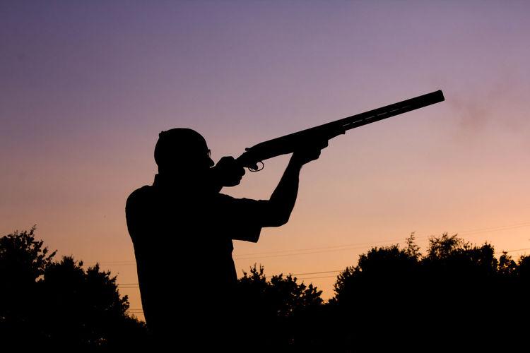 Silhouette Man Aiming Shotgun Against Clear Sky During Sunset
