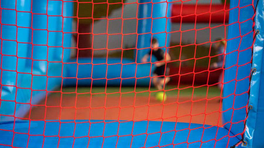 Close-up of net with man playing soccer in background