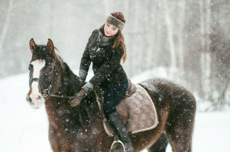 Adult Animal Animal Themes Beautiful People Beautiful Woman Cold Temperature Day Dog Domestic Animals Friendship Happiness Horseback Riding Mammal Nature One Animal One Person Outdoors People Pets Smiling Snow Snowflake Snowing Warm Clothing Winter