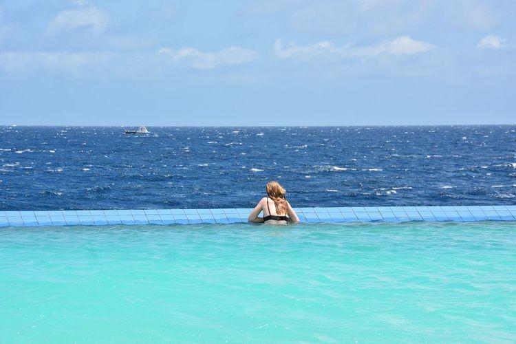 Girl swimming in infinity pool against sea