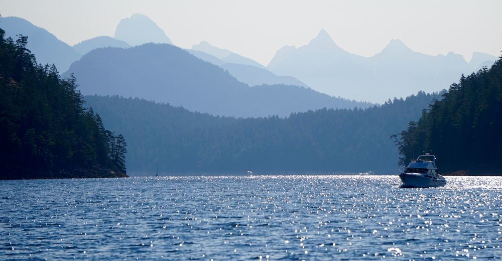 Boat sailing on lake by mountains against clear sky