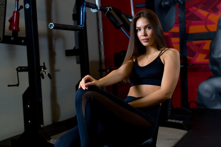 Portrait of young woman exercising at gym