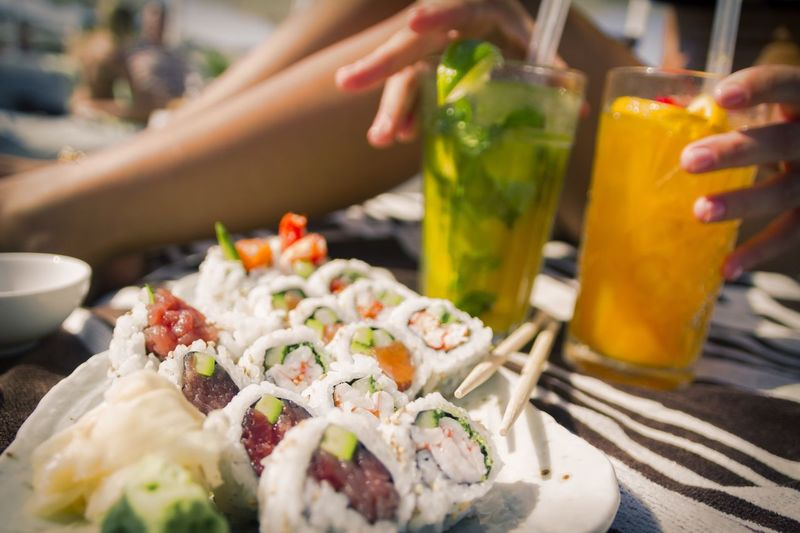 Close-Up Of Sushi With Woman Holding Cocktail Glasses