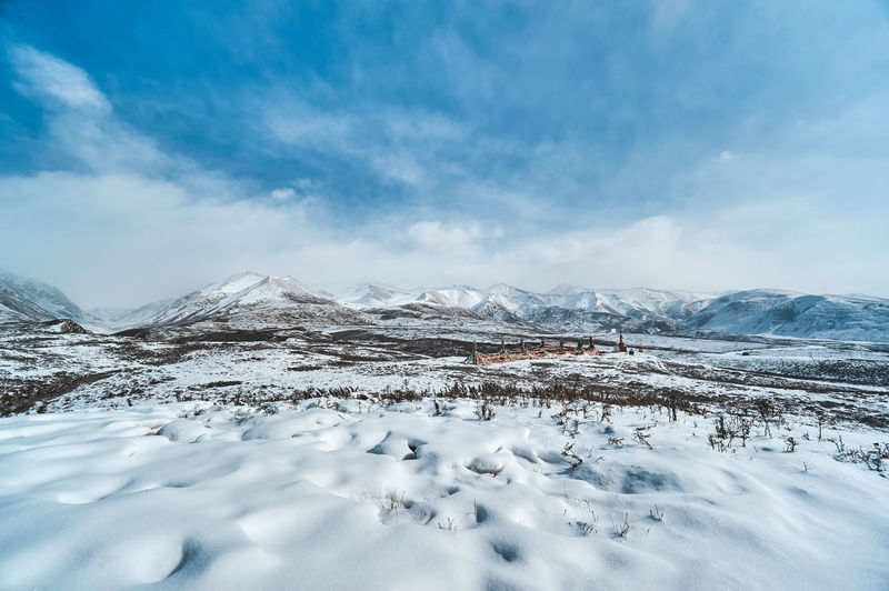 Scenic view of snow covered landscape against cloudy sky