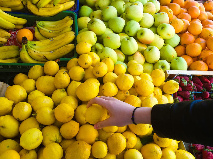 Cropped hand holding lemon at market stall